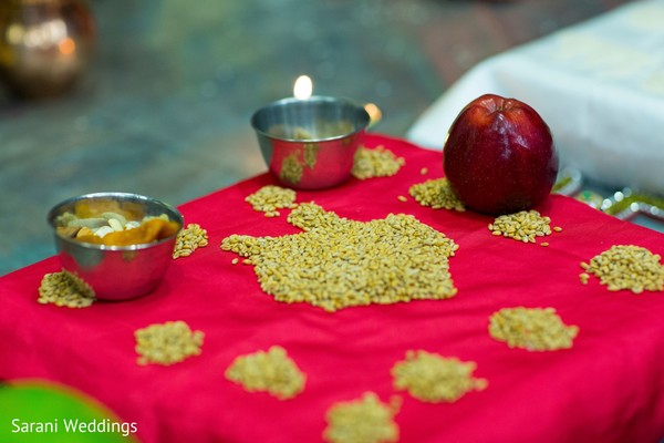 Indian wedding ceremony rice, apple, seeds and pots for ritual.