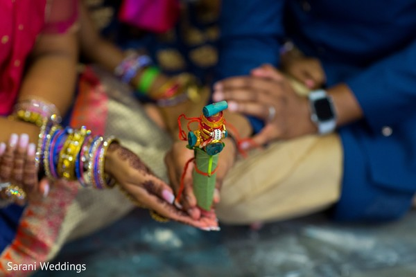 Indian bride and groom holding the wedding ceremony ritual items.