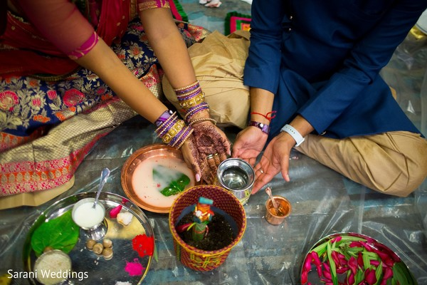 Indian bride and groom touching sacred pot.