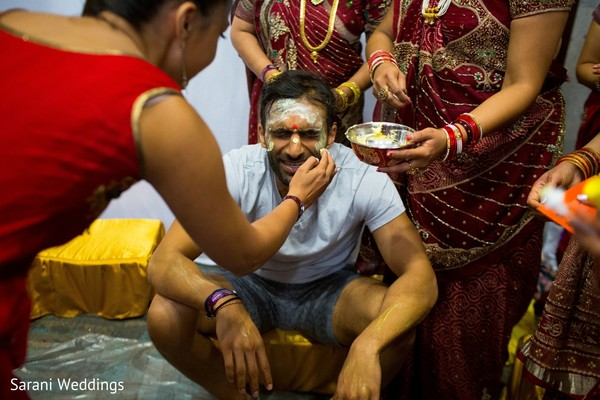 Indian groom getting cover with yellow paste.