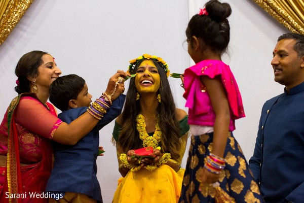 Indian bride with yellow paint on her face ritual.