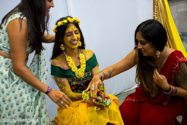 Indian bride being cover up with turmeric paste.