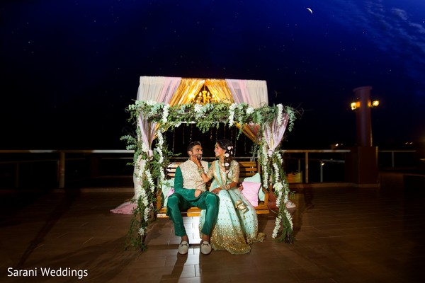 Indian couple posing at pre-wedding swing seat stage.