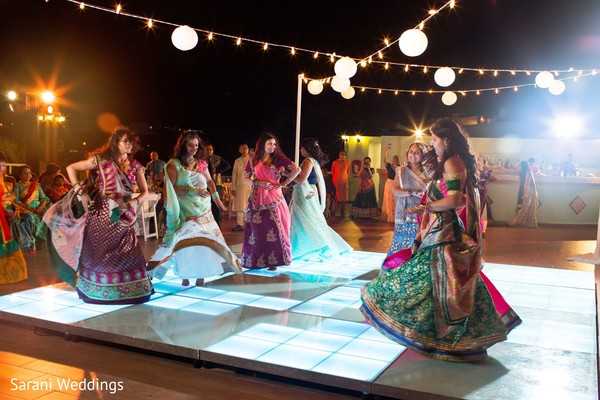 Indian bridesmaids dancing at sangeet lighted dance floor.