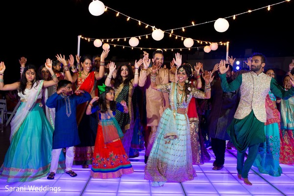 Indian bride dancing with guests at sangeet party.
