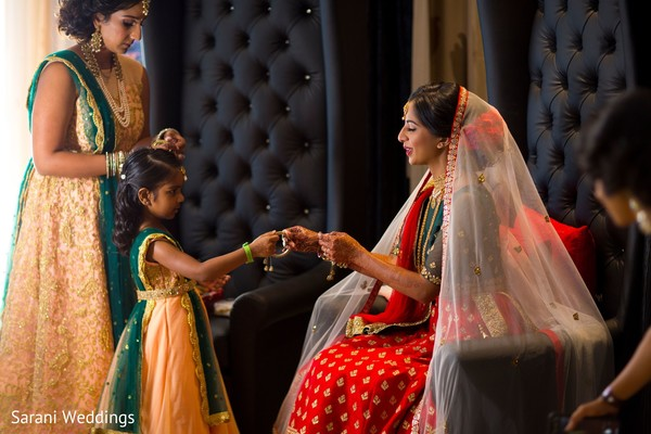 Indian bride getting her bangles from flower girl.