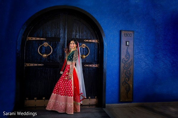 Indian bride on her red and green ceremony lehenga.