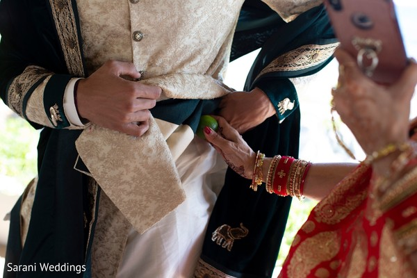 Maharani putting lemon on grooms pocket.