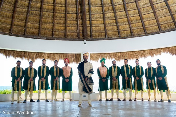 Indian groom with groomsmen on their green white and gold outfits.