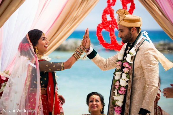 Indian couple holding hands at wedding ceremony.