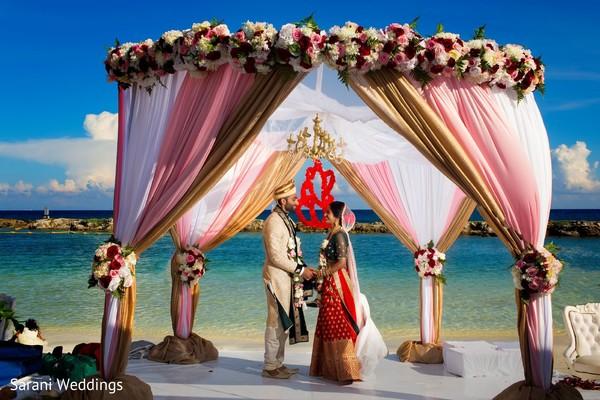 Indian couple posing at ceremony mandap.