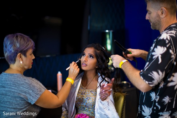 Indian bride getting her makeup and hair done.