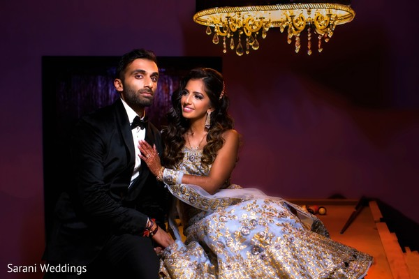 Indian bride and groom posing at pool table.