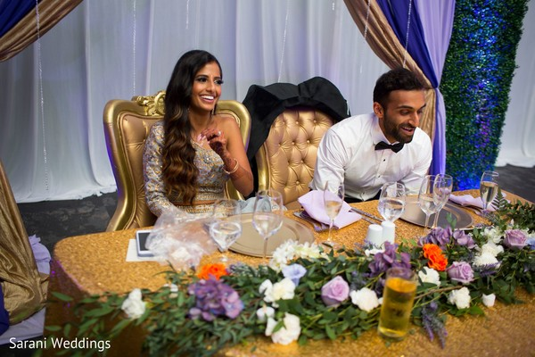 Indian bride and groom at their wedding reception table.