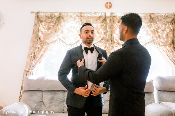 Indian relative helping the Indian groom with his suit