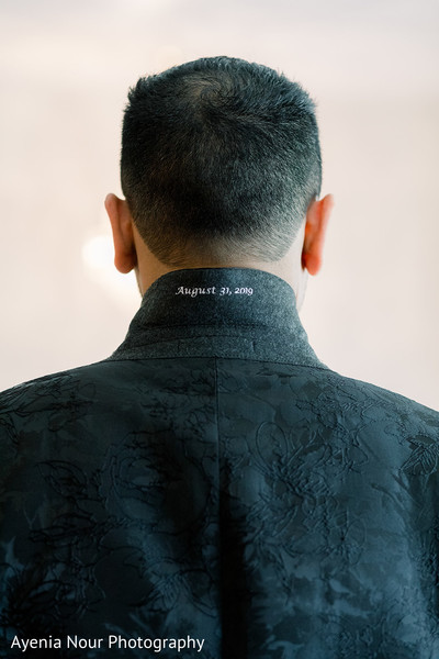 Indian groom showing the inscription on his suit jacket