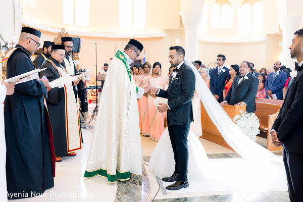 Indian groom getting the ring from the priest.