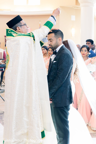Indian groom being blessed with holly watter.