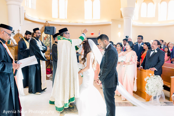 Indian groom being blessed by priest.