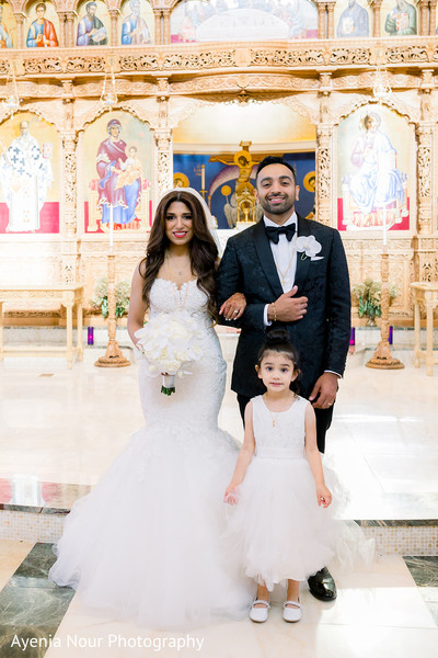 Indian couple posing with flower girl at church.