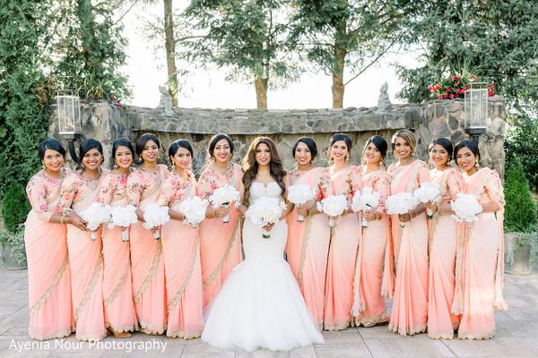 Indian bridesmaids posing with maharani outdoors.