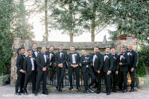 Indian groom with groomsmen on their black tuxedos.