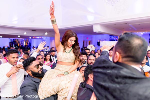 Maharani lifted by groomsmen at reception.