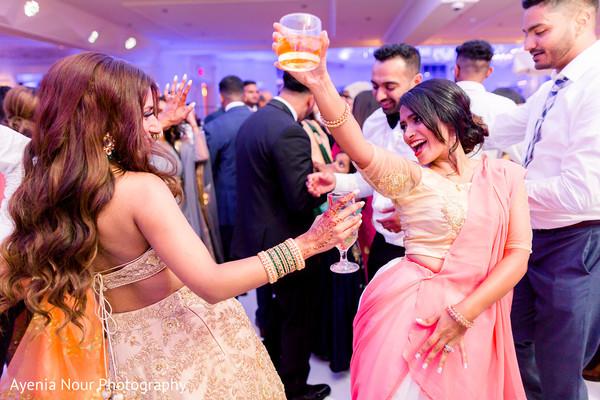 Indian bride dancing at reception.