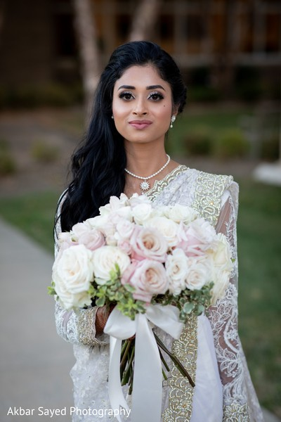 Indian bride holding her white and pink roses bouquet.