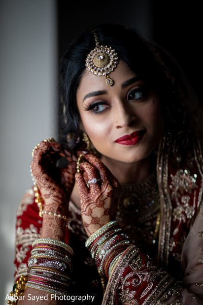 Indian bride putting on her ceremony earrings.