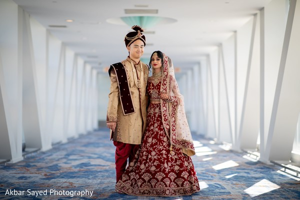 Indian couple on their golden and deep red ceremony outfits.