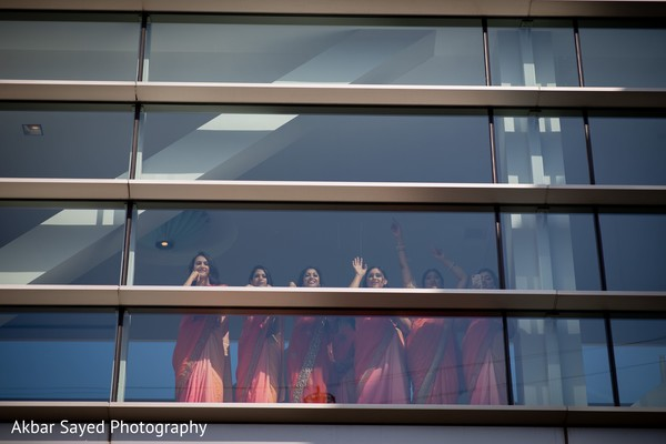 Indian bridesmaids waiving from venue window.