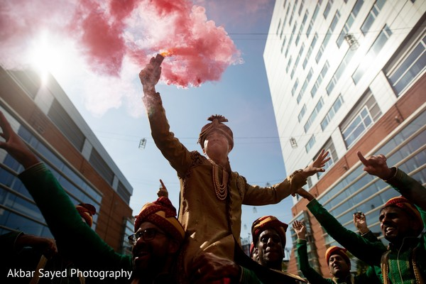 Indian groom holding a colored smoke stick.