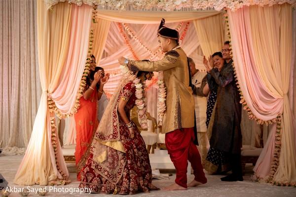 Indian groom putting garland to bride ritual.