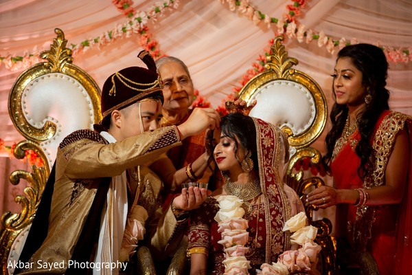 Indian groom putting red mark on maharani's forehead.