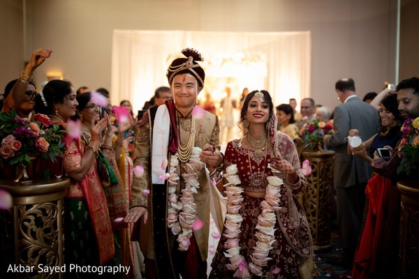 Indian couple walking out of wedding ceremony.