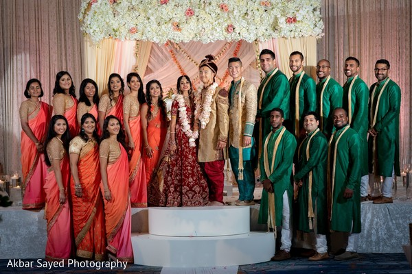 Indian couple posing with bridesmaids and groomsmen at mandap.