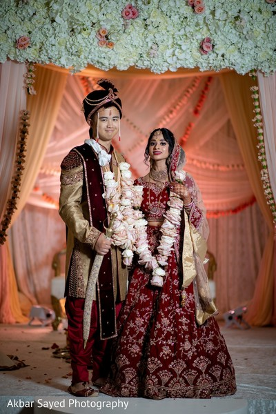Indian couple posing on their wedding ceremony outfits.