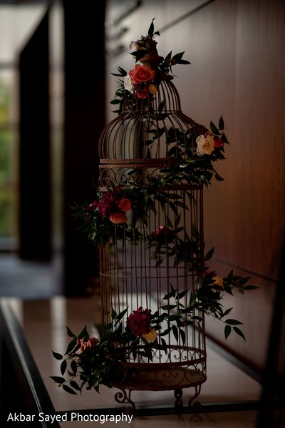Indian wedding table birdcage with roses decorations.