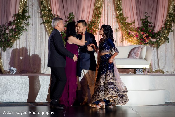 Indian bride and groom being blessed by grooms parents.