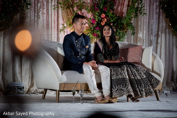 Indian couple seating on white reception stage sofa.