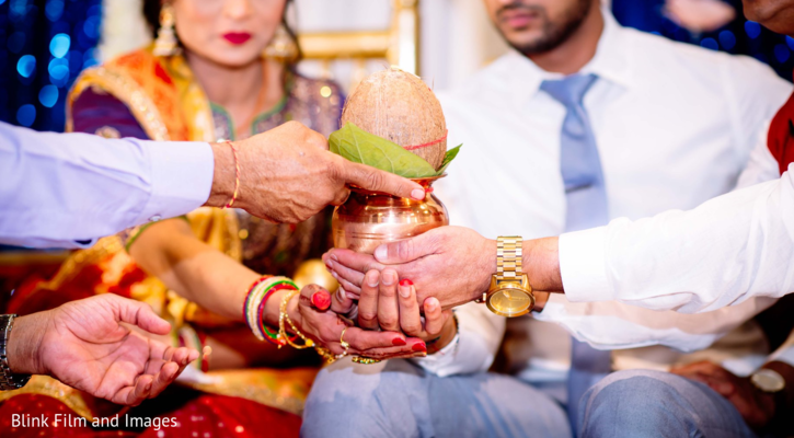 Several hands holding a coconut on a vase