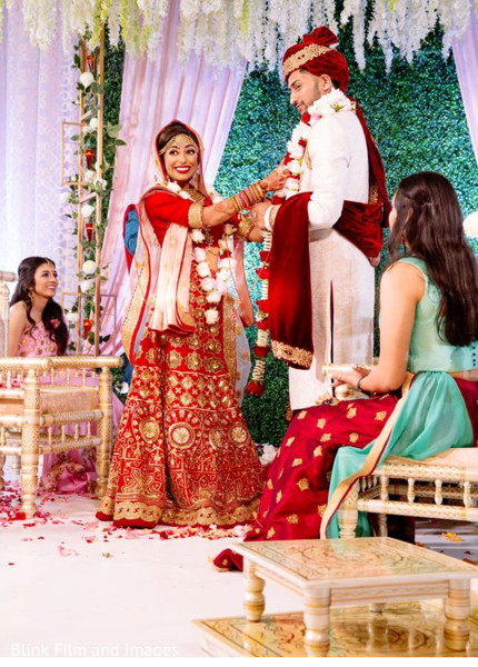 Indian bride putting a floral necklace on her Indian groom