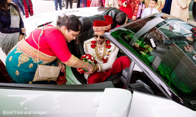 Indian groom handing an arrangement to an Indian relative