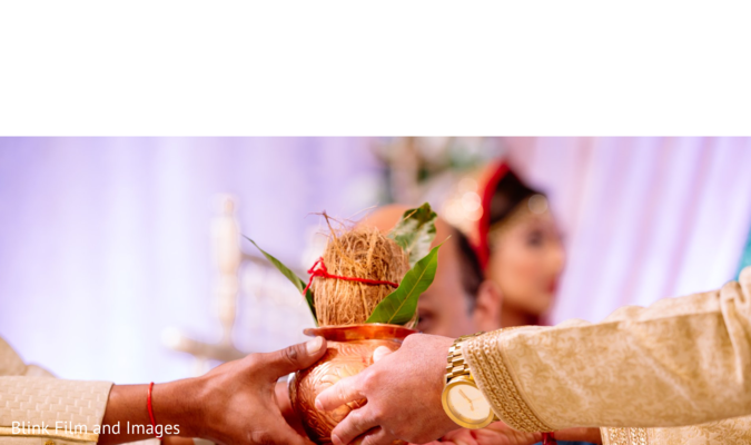Indian groom receiving a coconut in a vase