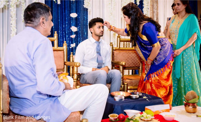 Indian relative painting a red spot on the Indian groom's forehead