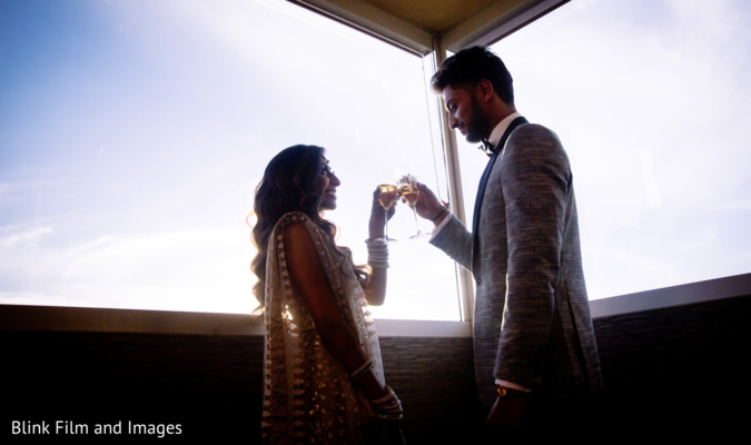 Indian newlyweds toasting on a terrace
