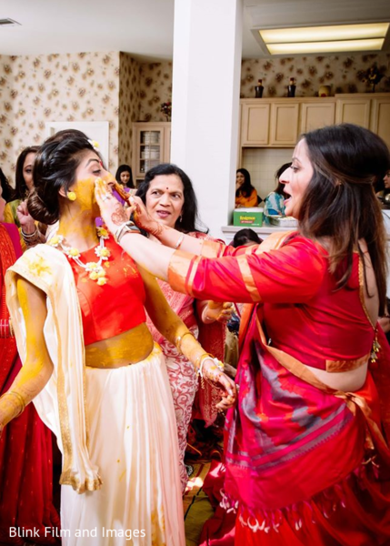 Indian relative applying tumeric paste to the Indian bride's face
