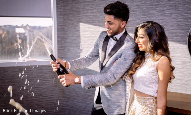 Indian groom opening a bottle of champagne with his Indian bride