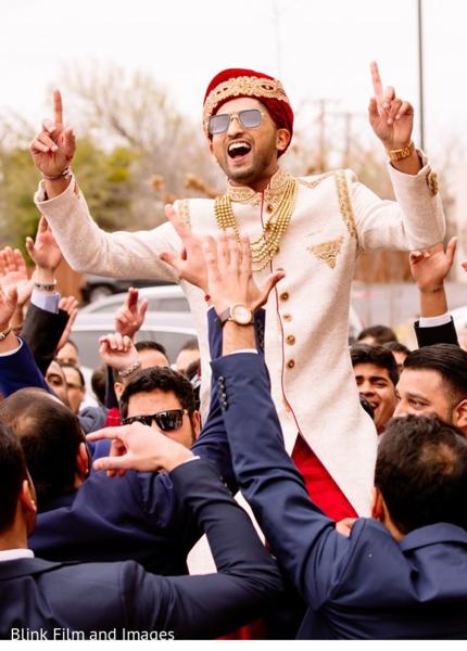 Indian groom carried in shoulders during Baraat